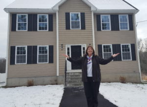 The winner of the House Raffle, Barbara Lang, stands in front of her new beige colonial with her arms up like a winner.